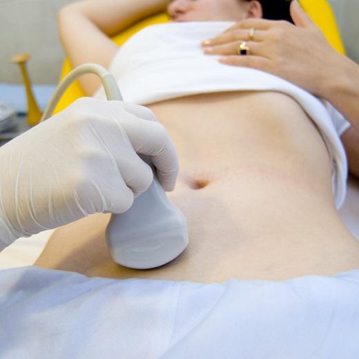 врач проводит датчиком по брюшной полости пациента
