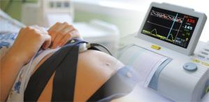 Женщина полулежа с прикрепелнными к животу датчиками во время проведения процедуры кардиотокографии
