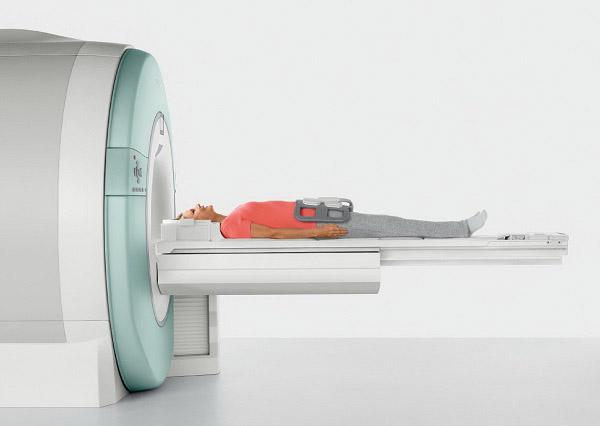 Пациент лежит на подвижном столе перед отверстием сканирующего блока томографа